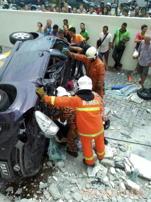 PENANG 14 August 2015. Anggota bomba dan penyelamat mengeluarkan mangsa pemandu kereta myvi yang terbabas dan terjunam dari tingkat tiga di Pangsapuri Taman Pekaka, Sungai Dua, Pulau Pinang. NSTP/Ihsan Pembaca