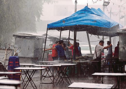 PENANG 08 August 2015. Orang ramai membantu memegang khemah peniaga di Pulau Tikus ketika hujang lebat dan angin kuat melanda beberapa kawasan sekitar Pulau Pinang NSTP/Mikail Ong