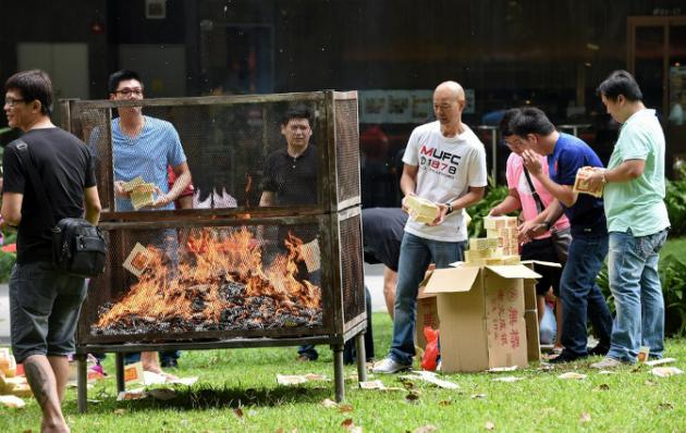 Employees from a nearby office building burn offerings to mark the Hungry Ghost Festival in Singapore on August 8, 2014. Superstition comes to the fore during the month-long Hungry Ghost Festival, which traditionally begins this time of year. Chinese superstition holds that the gates of hell are opened for spirits to wander across the mortal realm before they return to the underworld. AFP PHOTO / ROSLAN RAHMAN