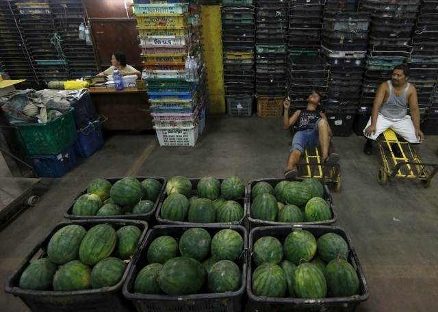 Workers take a break from unloading watermelon at a wholesale market in Kuala Lumpur, Malaysia, January 7, 2016. REUTERS/Olivia Harris